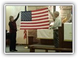 "Veteran's Day 2014- Veteran's Mike and Pat Reher hold up the American Flag while the congregation sings ""Battle Hymn of the Republic"""